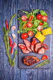 BBQ lamb steak with vegetable salad and corn on dark wooden back Royalty Free Stock Photography
