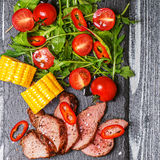 BBQ lamb steak with vegetable salad and corn on dark wooden back Stock Image
