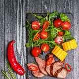 BBQ lamb steak with vegetable salad and corn on dark wooden back Royalty Free Stock Photo