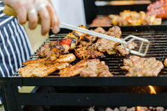 BBQ large grill with roasted meat, stew, sousages, chicken breas. T. Low angle perspective. Horizontal crop Royalty Free Stock Images