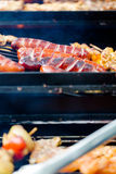 BBQ large grill with roasted meat, stew, sousages, chicken breas. T. Low angle perspective. Vertical crop Stock Images