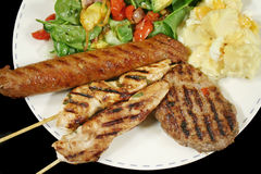 BBQ Lunch 6. BBQ chicken tenderloin skewers, beef sausage, beef patty with spinach salad and potato salad stock photography