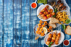 BBQ lunch assortment. Variety of BBQ snack lunch. Plates grilled spicy prawn kebabs, chicken, pork, vegetables, mushrooms skewers, bread, french fries potatoes stock photos