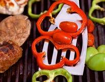 BBQ med hamburgare, pappers, tomater och champinjoner Royaltyfria Bilder