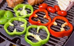 BBQ med hamburgare, pappers, tomater och champinjoner Fotografering för Bildbyråer