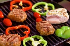 BBQ med hamburgare, pappers, tomater och champinjoner Royaltyfri Fotografi