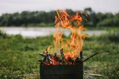 BBQ met brand houten aard dichtbij rivier stock afbeelding