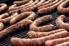 BBQ met vurige worsten op de grill Het rood bakte heerlijke sappige worsten in rij Smakelijke worst die op een barbecuegrill voor Royalty-vrije Stock Foto's