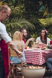 BBQ party in garden. A men grilling food in front of his friends sitting by a table with red and white checkered tablecloth at BBQ party in the garden stock photography