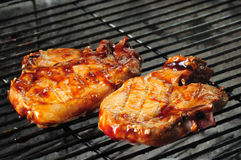 BBQ pork chops. Two bbq pork chops finishing on the grill Royalty Free Stock Image