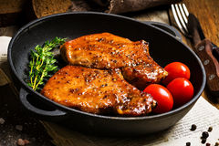 BBQ pork chops in sweet glaze. Grilled pork chops in sweet honey glaze, served in grill iron skillet with fresh thyme, rye bread and cherry tomatoes, close up Stock Photo