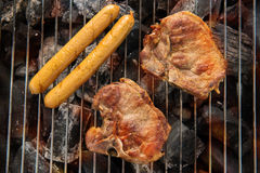 BBQ pork meat and sausages on the grill. Royalty Free Stock Image