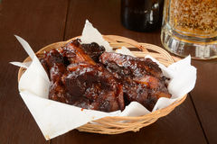 BBQ Pork Ribs and Beer. A basket of barbecued pork ribs with a mug of beer royalty free stock photos