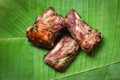Bbq pork ribs grilled with herbs spices served on banana leaf - Roasted barbecue pork spare rib sliced royalty free stock photo