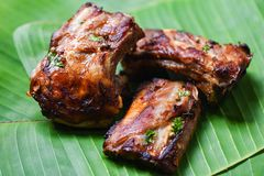Bbq pork ribs grilled with herbs spices served on banana leaf - Roasted barbecue pork spare rib sliced royalty free stock images