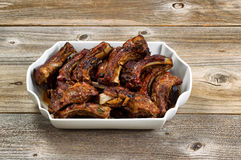 BBQ pork ribs in large plate on rustic wooden boards Royalty Free Stock Photo