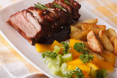 BBQ pork ribs with salad and fried potatoes close-up. horizontal Stock Photo