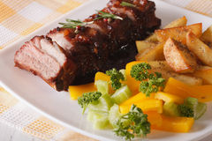 BBQ pork ribs with a side dish of vegetables close-up. Horizonta Stock Photos