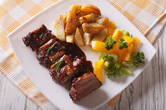 BBQ pork ribs with vegetables close-up on a plate. horizontal to Royalty Free Stock Photo
