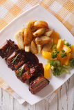 BBQ pork ribs with vegetables close-up on a plate. vertical top Stock Images