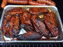 BBQ Pork Spare Ribs. With Bratwurst on the smoker grill Stock Photos
