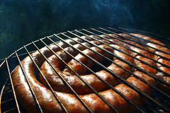 BBQ raw fiery sausages on the grill. BBQ with fiery sausages on the grill Royalty Free Stock Photo