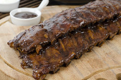 BBQ Ribs. Marinated pork ribs with barbeque sauce dip royalty free stock photo