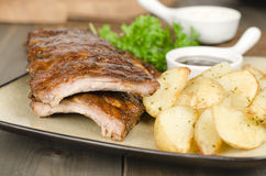 BBQ Ribs. Marinated pork ribs with barbeque dipping sauce and potato wedges with sour cream dip royalty free stock image