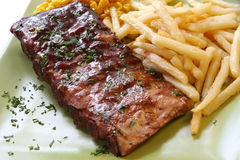 BBQ Ribs. BBQ marinated spareribs and fries, with sweet corn Royalty Free Stock Images