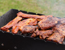 Bbq ribs and bacon on a grill with charcoal Stock Photography