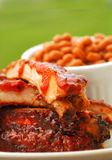 BBQ Ribs with beans and dipping sauce. Slab of BBQ spare ribs with beans and dipping sauce stock photo