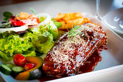 BBQ Ribs - Marinated pork ribs with salad, french fries and barb Royalty Free Stock Photos