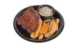 Bbq ribs plate on white. Picnic serving of bbq babyback ribs with fries and cole slaw Royalty Free Stock Image