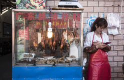 BBQ duck shop woman. The store-keeper takes a break to check her Wechat account between selling delicious BBQ roast duck from a small laneway cart royalty free stock photos