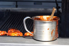 BBQ Sauce. Steel container full of bbq sauce next to a grill royalty free stock photos