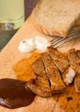 BBQ sauce with pork steak portion on wooden chopping board stock image