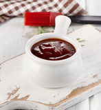 BBQ sauce in a white bowl. With a brush and fresh rosemary stock images