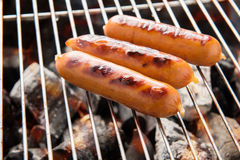 BBQ sausage on a flaming BBQ grill Stock Photo