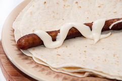 BBQ Sausage with mayonnaise on a Mexican tortilla Stock Photos