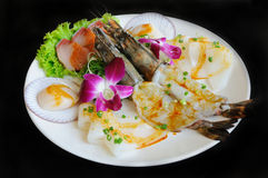 BBQ seafood. On the plate and decorated with orchid , black background Royalty Free Stock Photo