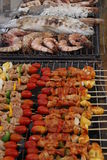 BBQ and Seafoods. Roasting BBQ sticks and seafoods on a grill Royalty Free Stock Image
