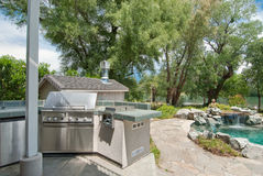 BBQ setup and pool view. Nice BBQ setup and view of the river and pool / waterfall Stock Photo
