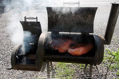 BBQ Smoker Grill. Barbecue smoker with brisket and pork. Pleasant aroma. Horizontal Stock Image