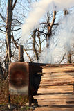 BBQ smoker with wood pile. Home made smoker in a rural location with stacked wood Royalty Free Stock Photo