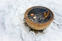 BBQ Snacks in Cold Winter. Barbeque snacks using a fire bowl in cold winter snow royalty free stock images