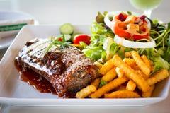 Bbq-stöd - marinerade grisköttstöd med sallad, fransmansmåfiskar och taggen Royaltyfri Foto