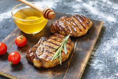Bbq, Grilled beefsteaks, rosemary, honey, wooden cutting board, dinner preparation, closeup. copy space, selective focus, Royalty Free Stock Photography