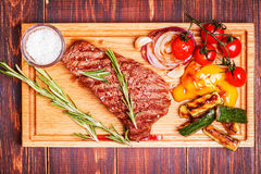 BBQ steak with grilled vegetables on cutting board stock photo