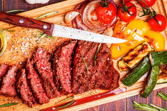 BBQ steak with grilled vegetables on cutting board. On dark wooden background Royalty Free Stock Image