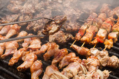 Bbq steaks and meat grilled on brazier served by man Stock Images